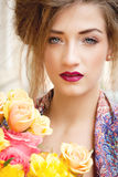 Attractive young woman with pink roses. Outdoor on street Stock Photography