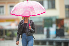 Attractive young woman with pink  umbrella in the rain and strong wind. Girl with umbrella in autumn weather Stock Images