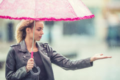 Attractive young woman with pink  umbrella in the rain and strong wind. Girl with umbrella in autumn weather Royalty Free Stock Photography