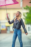 Attractive young woman with pink  umbrella in the rain and strong wind. Girl with umbrella in autumn weather Royalty Free Stock Photos