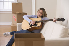 Attractive Young Woman Playing the Guitar Stock Photos