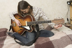 Attractive young woman playing guitar Stock Photos