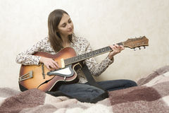 Attractive young woman playing guitar. On grey background Stock Photo