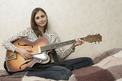 Attractive young woman playing guitar. Royalty Free Stock Photos