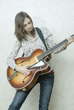 Attractive young woman playing guitar Royalty Free Stock Photos