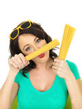 Attractive Young Woman Playing with Holding Handfulls of Dried Pasta Royalty Free Stock Photos