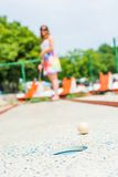 Attractive young woman playing mini golf. Royalty Free Stock Photos