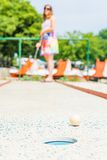 Attractive young woman playing mini golf. Royalty Free Stock Images