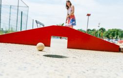 Attractive young woman playing mini golf. Stock Image