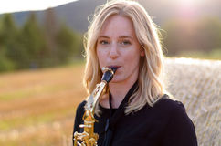 Attractive young woman playing a tenor saxophone Stock Image