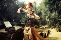 Attractive young woman playing on violin outdoors. Stock Photo