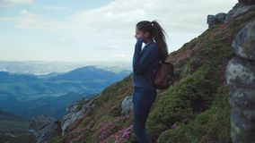 Attractive young woman with ponytail, in sport wear goes down the path on the top of the mountain, standstill and stock footage