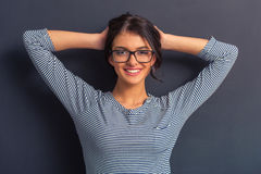 Attractive young woman. Portrait of attractive young woman in eyeglasses looking at camera and smiling, standing with hands behind head against dark background Stock Photo