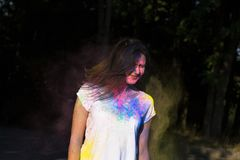 Attractive brunette girl posing with exploding Gulal powder in t. Attractive young woman posing with exploding Holi powder in the park Royalty Free Stock Photography