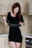 Attractive young woman posing in a kitchen setting Royalty Free Stock Images