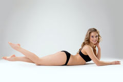 Attractive young woman posing lying in studio Stock Images