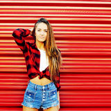 Attractive young woman posing near a red wall - copyspace Royalty Free Stock Photos