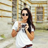 Attractive young woman posing with old camera wearing sunglasses Royalty Free Stock Photography