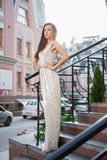 Attractive young woman posing outdoors. On a background of buildings standing on the stairs dressed in a long silver dress stock photo