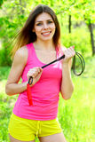 Attractive young woman posing in a park with a skipping rope Stock Photo