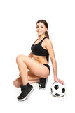 Attractive young woman posing with a soccer ball on a white back Stock Image