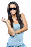 Attractive young woman posing in studio wearing sunglasses Royalty Free Stock Image