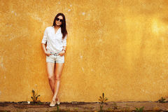 Attractive young woman posing by the wall Royalty Free Stock Image