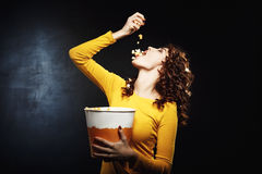 Attractive young woman pouring popcorn in mouth holding big bucket. Attractive young woman pouring popcorn in mouth holding bucket. Movie theatre. Isolated on Stock Photo