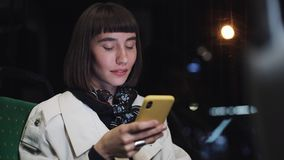 Attractive young woman in public transport using a mobile phone. She is texting, checking mails, chats or the news. Online. City lights background stock video footage