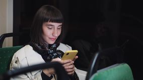 Attractive young woman in public transport using a mobile phone. She is texting, checking mails, chats or the news. Online. City lights background stock footage