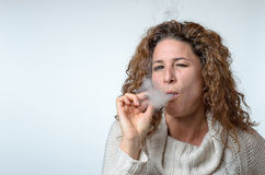 Attractive young woman puffing on a cigarette Stock Photo