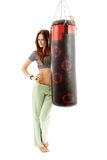 Attractive young woman with punching bag Royalty Free Stock Image