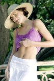 Attractive young woman in purple vest, sun hat and white skirt,. Attractive young woman on a foot bridge in Central Park, New York, Manhattan, USA royalty free stock photo