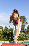 Attractive young woman putting golf ball on green Stock Images