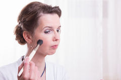 Attractive young woman is putting her make up on Stock Photos