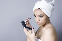 Attractive young woman putting on makeup Stock Photo