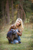 Attractive young woman with raccoon. Portrait of attractive young woman with raccoon in a forest royalty free stock image