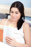 Attractive young woman  reading  a book in bed Royalty Free Stock Photography