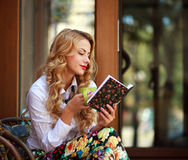 Attractive young woman reading book while drinking coffee Stock Photos