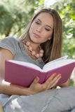 Attractive young woman reading book in park Royalty Free Stock Photography