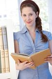 Attractive young woman reading at home smiling. Attractive young woman standing by bookshelf at home, reading book, smiling Royalty Free Stock Photo
