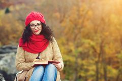 Attractive young woman reads book in a park and enjoys sunny autumn day. Stock Photo