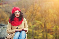 Attractive young woman reads book in a park and enjoys sunny autumn day. Royalty Free Stock Photos