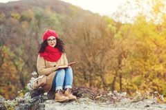 Attractive young woman reads book in a park and enjoys sunny autumn day. Stock Photos