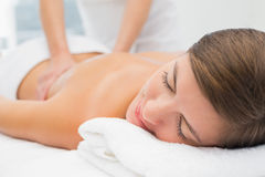 Attractive young woman receiving back massage at spa center. Close up of an attractive young woman receiving back massage at spa center stock image