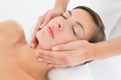 Attractive young woman receiving facial massage at spa center Royalty Free Stock Image
