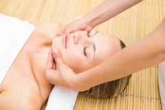 Attractive young woman receiving facial massage at spa center Stock Photo