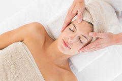 Attractive young woman receiving facial massage at spa center Stock Images