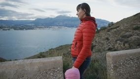 Attractive young woman in red bubble jacket walking with toddler in the rose hood on a mountain road on the coast. Landscape background stock video footage