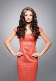 Attractive, young woman in a red dress wearing a golden luxury headband Stock Image